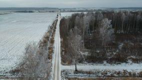 农田石渣路在冬天和冷淡的森林,鸟瞰图 股票录像