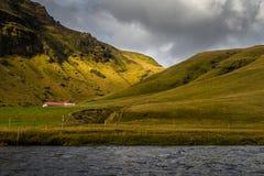 农舍周围绿色领域有河foregroundand山脉背景 库存照片