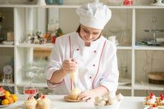 冠上与奶油的糖果商画象一块杯形蛋糕 免版税图库摄影