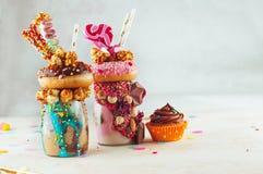冠上与油炸圈饼、玉米花和甜点的两个离经叛道之人的震动 免版税图库摄影