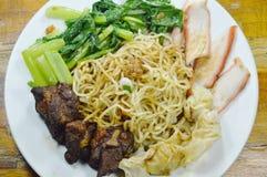 冠上切片的中国鸡蛋面烤与倾销穿戴的甜黑调味汁的猪肉和炖煮的食物肋骨在板材 库存照片