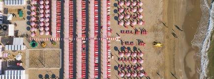 冠上在伞和眺望台的寄生虫鸟瞰图下在意大利沙滩 里乔内,意大利 亚得里亚海的海岸 免版税库存照片