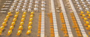 冠上在伞和眺望台的寄生虫鸟瞰图下在意大利沙滩 里乔内,意大利 亚得里亚海的海岸 库存照片