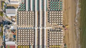 冠上在伞和眺望台的寄生虫鸟瞰图下在意大利沙滩 里乔内,意大利 亚得里亚海的海岸 免版税库存图片