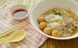 冠上煮沸的剁碎的猪肉和虾球在汤的大面条用辣味番茄酱 免版税图库摄影