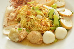 冠上鱼和虾球与切片的干辣中国黄色面条煮沸了猪肉在板材 免版税库存图片