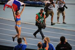 冠军E 跑与俄国旗子的伊辛巴耶娃 免版税库存图片