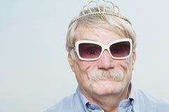 戴冠状头饰和太阳镜的老人 图库摄影