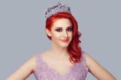 冠的红头发人在紫罗兰色颜色鞋带礼服的妇女有紫色珍珠的和水晶 库存图片