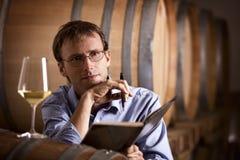 冥想在地窖里的酒生产者。 免版税库存图片