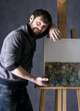 冥想油漆的艺术家摆在帆布旁边和,描述一个梦想 免版税图库摄影