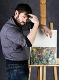 冥想油漆的艺术家摆在帆布旁边和,描述一个梦想 免版税库存照片