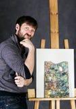 冥想油漆的艺术家摆在帆布旁边和,描述一个梦想 图库摄影