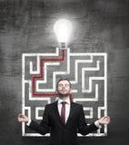 冥想的人和解决的迷宫与一个电灯泡在黑粉笔板 库存照片