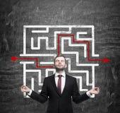 冥想的人和解决的迷宫与一个红色箭头在黑粉笔板 免版税库存照片