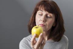 冥想维生素的美丽的成熟妇女黄色金黄苹果节食 图库摄影