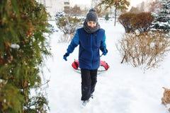 冬天、休闲和娱乐概念 水兵戏剧的逗人喜爱的年轻男孩与雪,获得乐趣,微笑 少年去与管 免版税库存图片