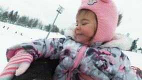冬天、休闲和娱乐概念-滑在雪管的小山下的愉快的小女孩 影视素材