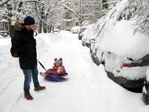 冬天、城市、爸爸和快乐的孩子雪撬的 库存图片