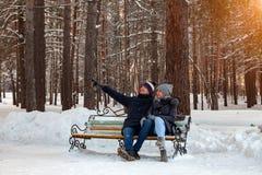 冬天下午,在夹克的一对爱恋的夫妇和帽子坐一条长凳在拥抱人展示的雪的森林 免版税库存照片