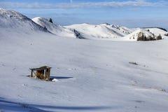 冬天与小木高山村庄的山背景,在雪原 免版税图库摄影