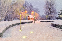 冬天与有启发性偏僻的房子的夜风景在下跌的雪冬天风景视图下 免版税库存图片