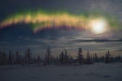 冬天与森林、月亮和北极光的夜风景在森林 免版税图库摄影