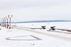 冬天与积雪的堤防和被冰的湖的城市风景 免版税库存照片