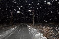 冬天与路的夜风景在雪的一个领域 降雪、飞雪和黑暗的天空 库存照片