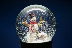 冬天与雪人的雪地球在蓝色 库存照片