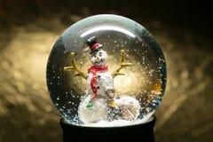冬天与雪人的雪地球在金子 免版税图库摄影