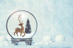 冬天与驯鹿形象的雪地球 免版税库存图片