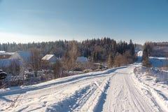 冬天乡下公路和村庄 免版税库存照片