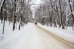 冬天农村路通过斯诺伊森林 免版税图库摄影
