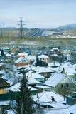 冬天初期,在第一雪下的村庄在兰色薄雾 图库摄影