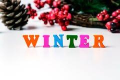 冬天到来的概念  地板标示用在一张白色桌上的色的信件,在锥体和f背景  免版税库存照片