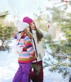 冬天和人概念-有孩子的母亲装饰树 免版税库存图片