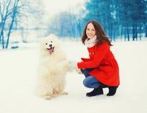 冬天和人们-获得愉快的微笑的少妇的所有者与白色萨莫耶特人狗的乐趣户外 免版税库存照片