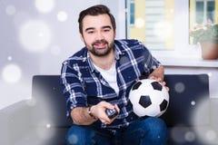 冬天和足球概念-愉快的在电视的人观看的橄榄球 图库摄影
