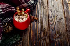冬天咖啡饮料、可可粉与打好的奶油和蛋白软糖在一个红色陶瓷杯子 站立在一张木桌上,在a旁边 库存照片