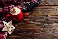 冬天咖啡饮料、可可粉与打好的奶油和蛋白软糖在一个红色陶瓷杯子 站立在一张木桌上,在a旁边 免版税库存图片