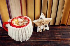 冬天咖啡饮料、可可粉与打好的奶油和蛋白软糖在一个红色陶瓷杯子 站立在书架,在圣诞节附近 库存照片