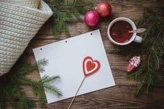冬天图片:一杯茶、冷杉分支、圣诞节装饰、围巾和纸片与心脏的在棍子 免版税图库摄影