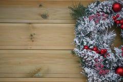 冬天圣诞节在雪盖的花圈的摄影图象用在自然木背景的红色莓果 免版税库存照片