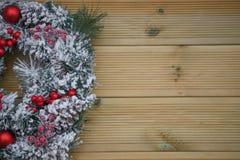 冬天圣诞节在雪盖的花圈的摄影图象用在自然木背景的红色莓果 库存图片