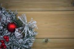 冬天圣诞节在雪盖的花圈的摄影图象用在自然木背景的红色莓果 免版税库存图片