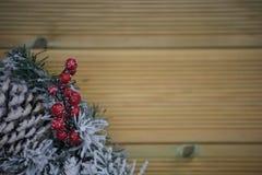 冬天圣诞节在雪盖的花圈的摄影图象用在自然木背景的红色莓果 库存照片
