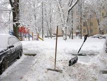 冬天在城市,手工从雪,铁锹清洗 免版税库存图片