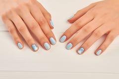 冬天在女性手上的设计修指甲 免版税库存照片