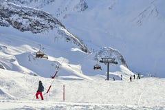 冬天在山之间的手段和滑雪倾斜在背景 库存图片